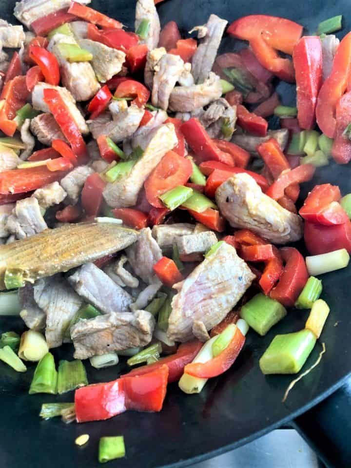 red peppers spring onions and slices of pork in wok