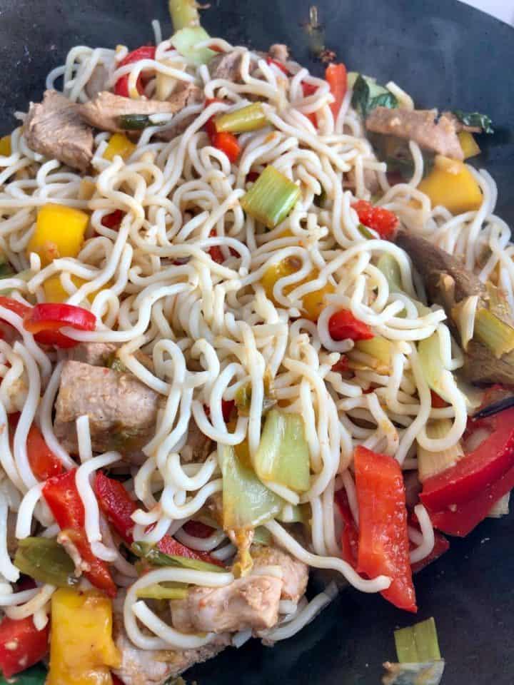 pork stir fry ingredients with noodles in wok