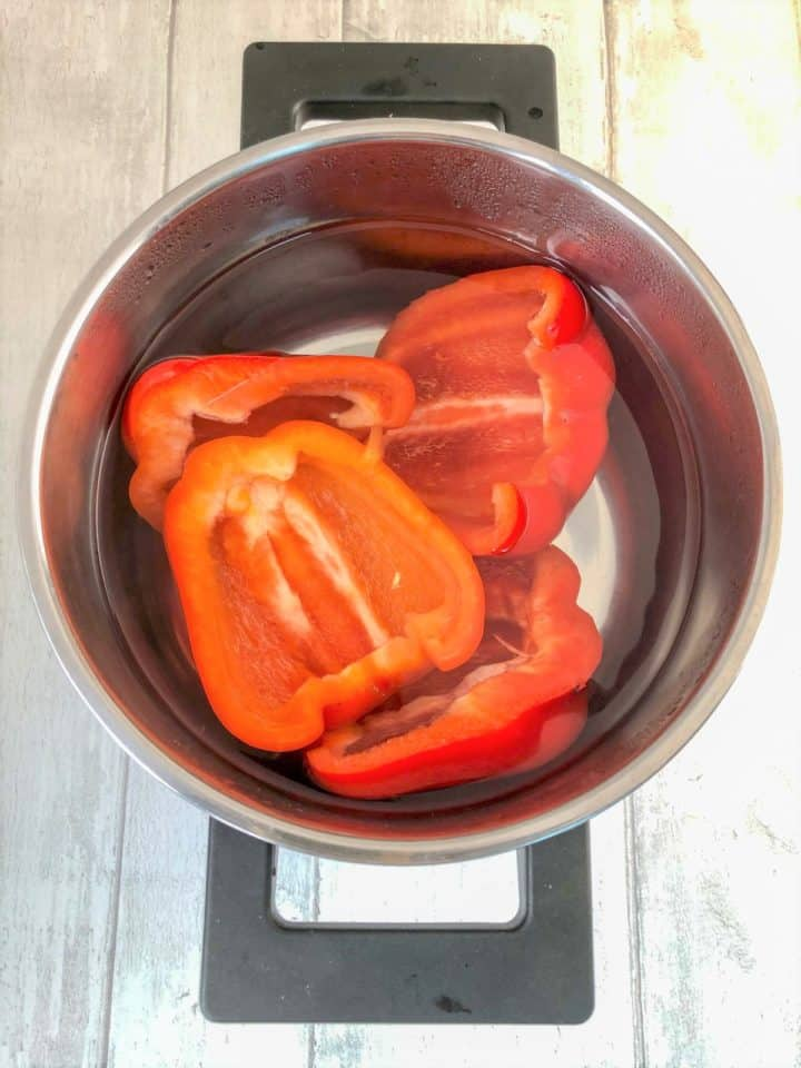 red pepper halves boiling in pan
