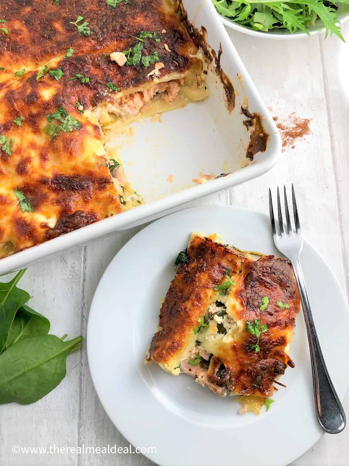 salmon and spinach lasagne in tray with separate slice on plate