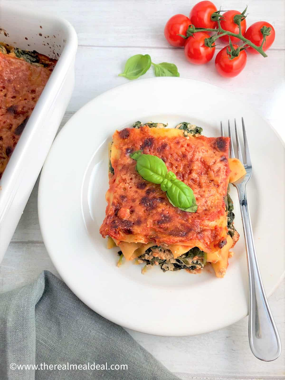 Spinach and Ricotta lasagne portion on plate with fork cherry tomatoes and basil leaves in background