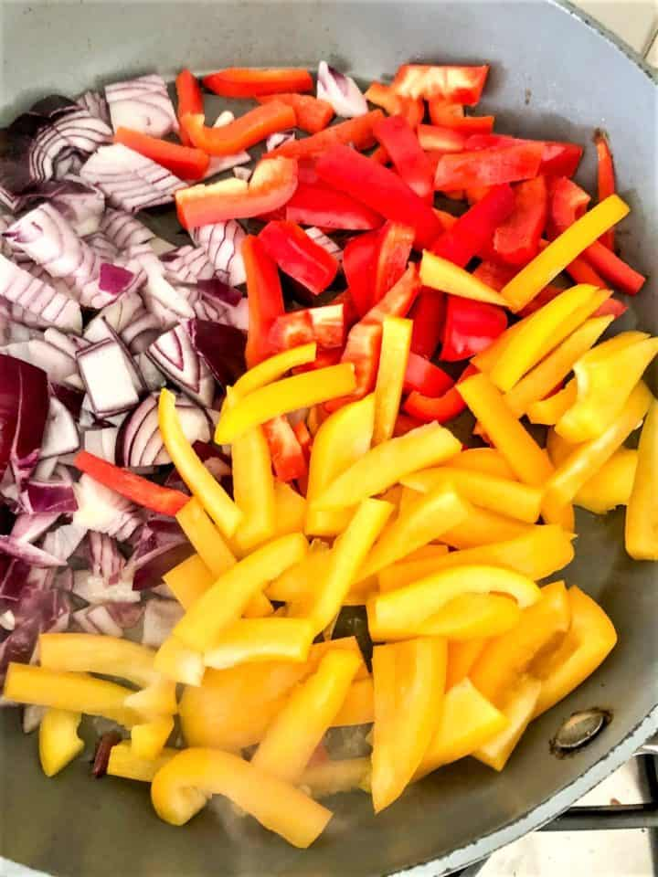 red onion red and yellow peppers frying in pan