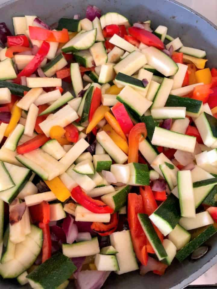 red onion red and yellow peppers and courgette frying in pan