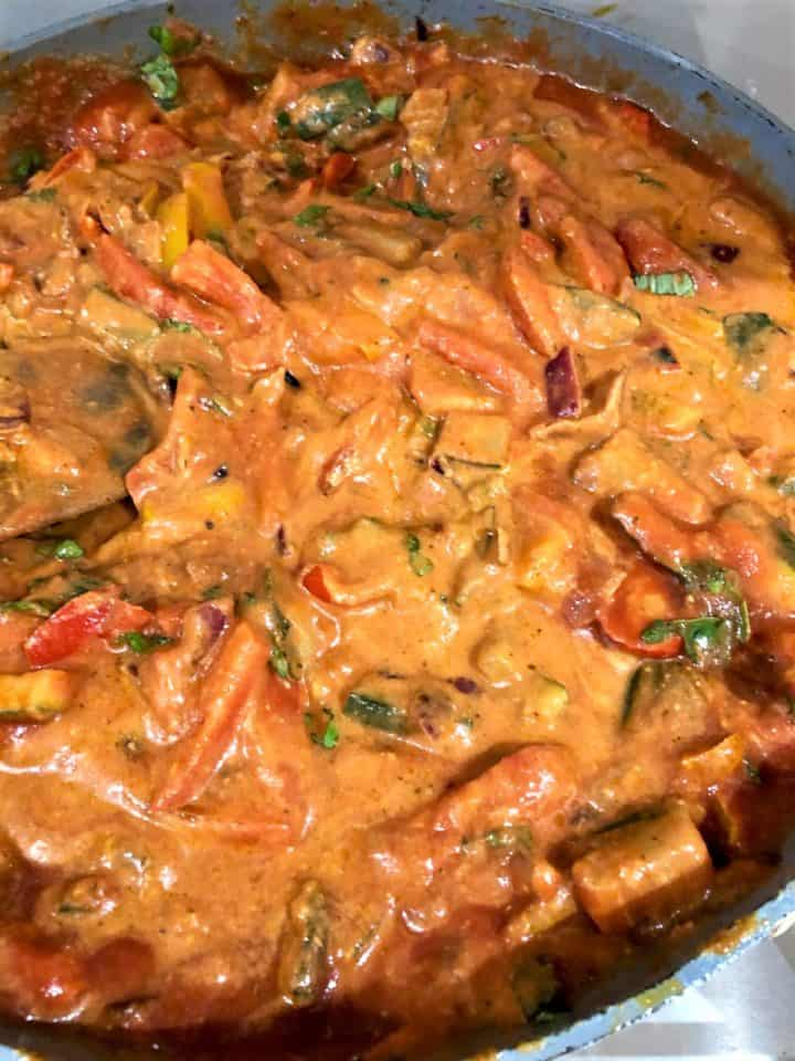 vegetables in sauce with red pesto cream cheese and passata fresh basil leaves