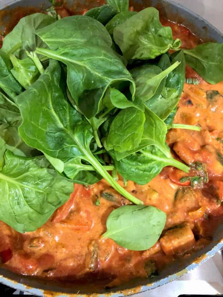 fresh spinach added to pasta bake sauce