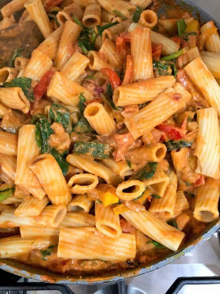 pasta stirred into sauce for pasta bake