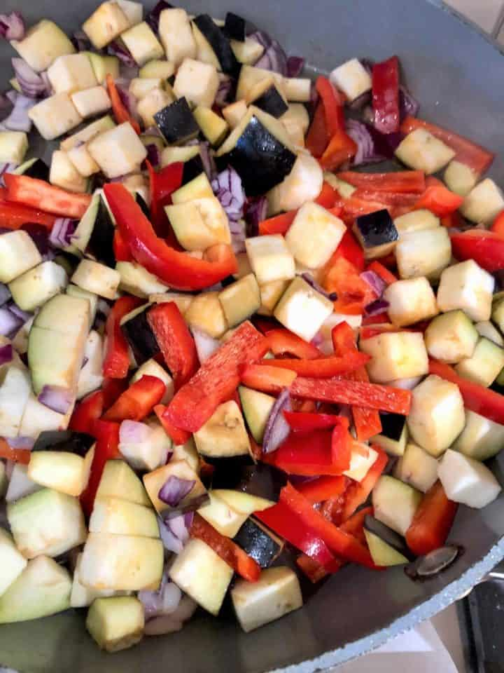 diced red onions red peppers aubergine in frying pan
