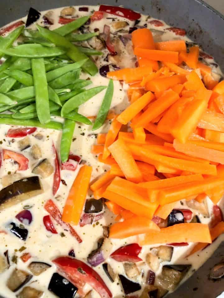 sliced carrots mangetout coconut milk added to pan with red onion red pepper and aubergine