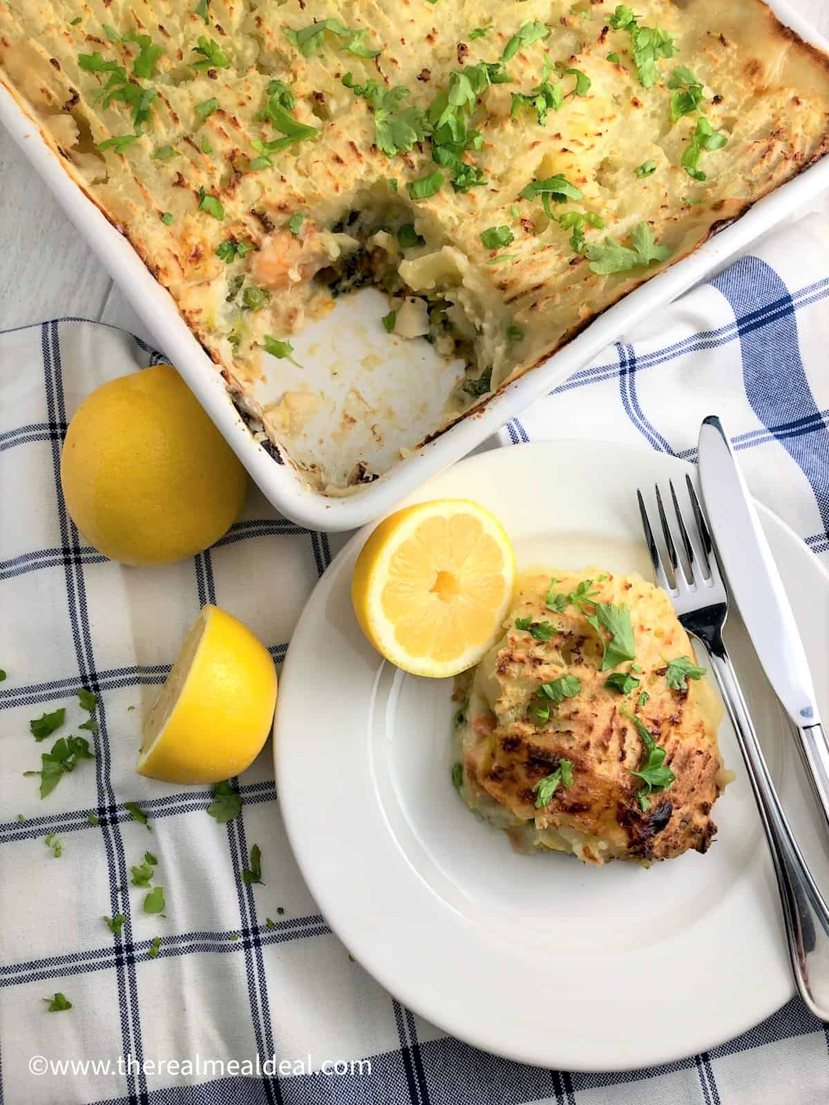 baked fish pie with leeks in dish with portion removed to plate at side served with lemon halves and fresh parsley leaves