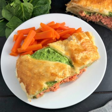 sliced of salmon en croute baked on plate with carrots spinach and remainder of en croute in background