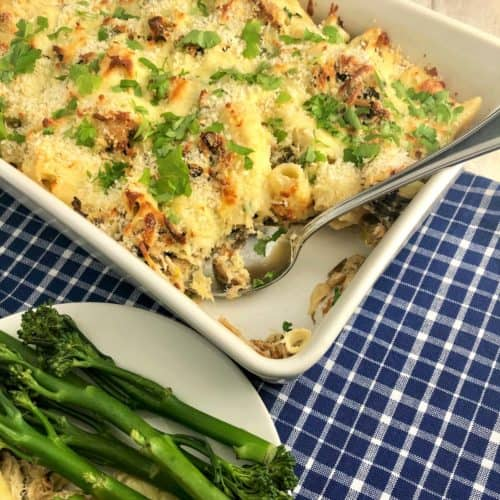 smoked mackerel pasta bake in dish topped with fresh parsley leaves with portion removed and on plate to side with broccoli