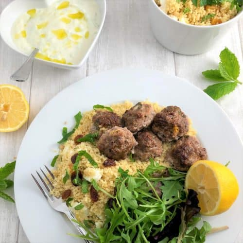 lamb meatballs served on bed couscous with apricots and sultanas and green salad and lemon with bowl greek tzatziki to side and bowl couscous to side