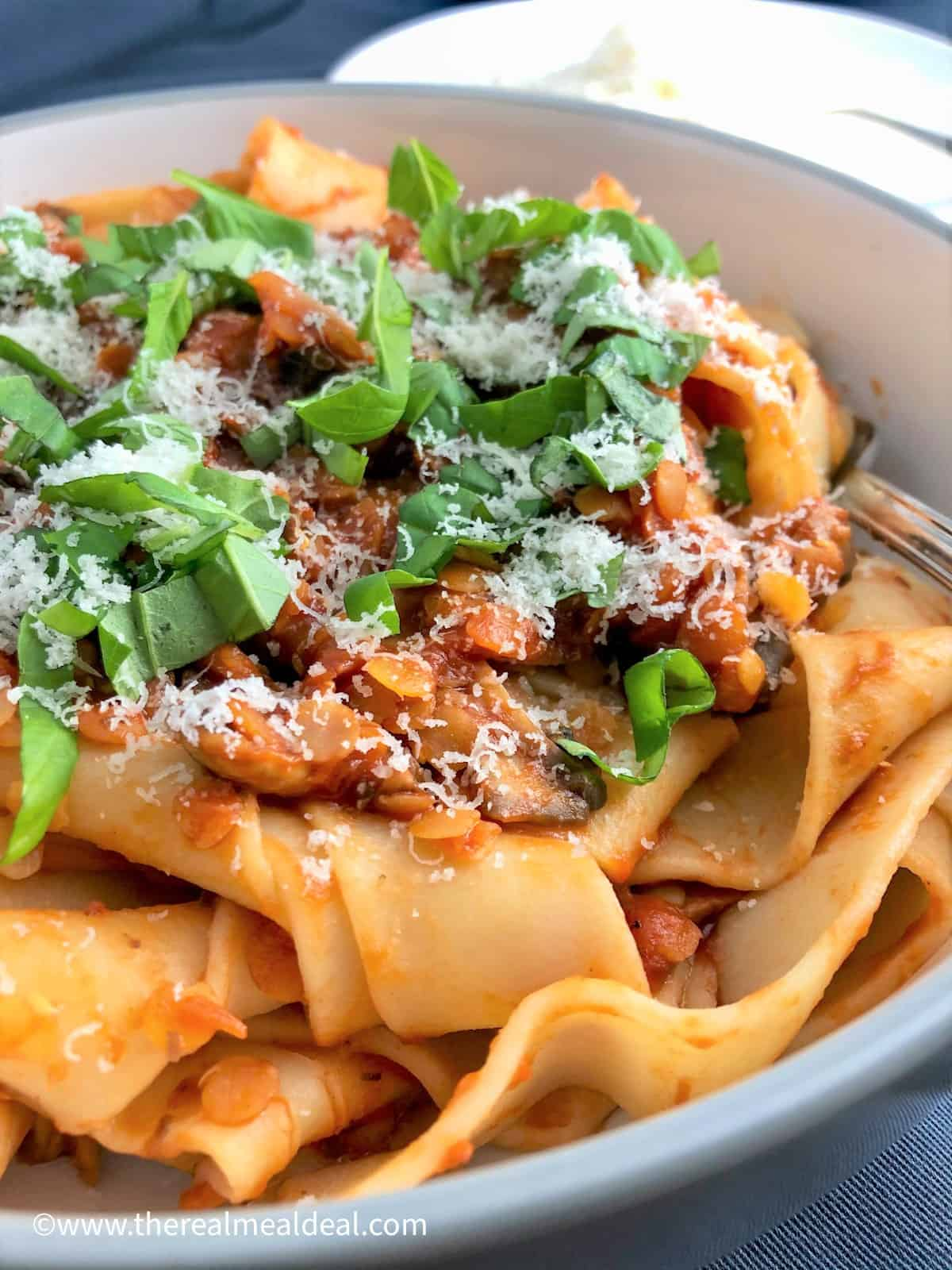 mushroom and lentil ragu served on papadelle pasta topped with fresh basil leaves and parmesan cheese