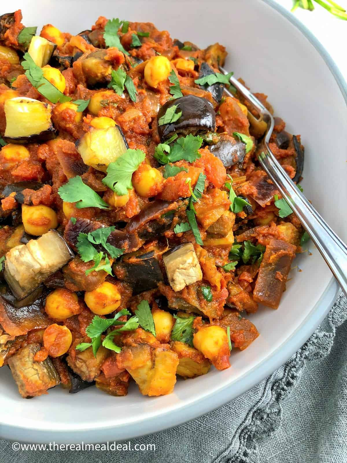 Aubergine and chickpea curry in bowl topped with fresh coriander leaves