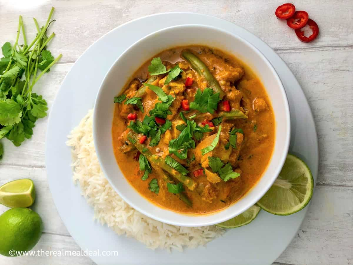 Creamy keralan fish curry in bowl with white rice, lime wedges and topped with fresh coriander leaves