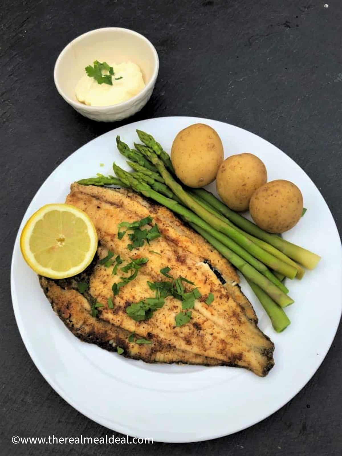 pan fried plaice with new potatoes and asparagus on plate