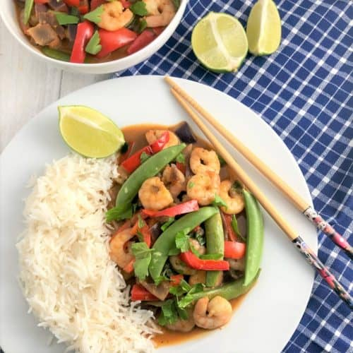 prawn red thai curry with white rice plated with chopsticks to side