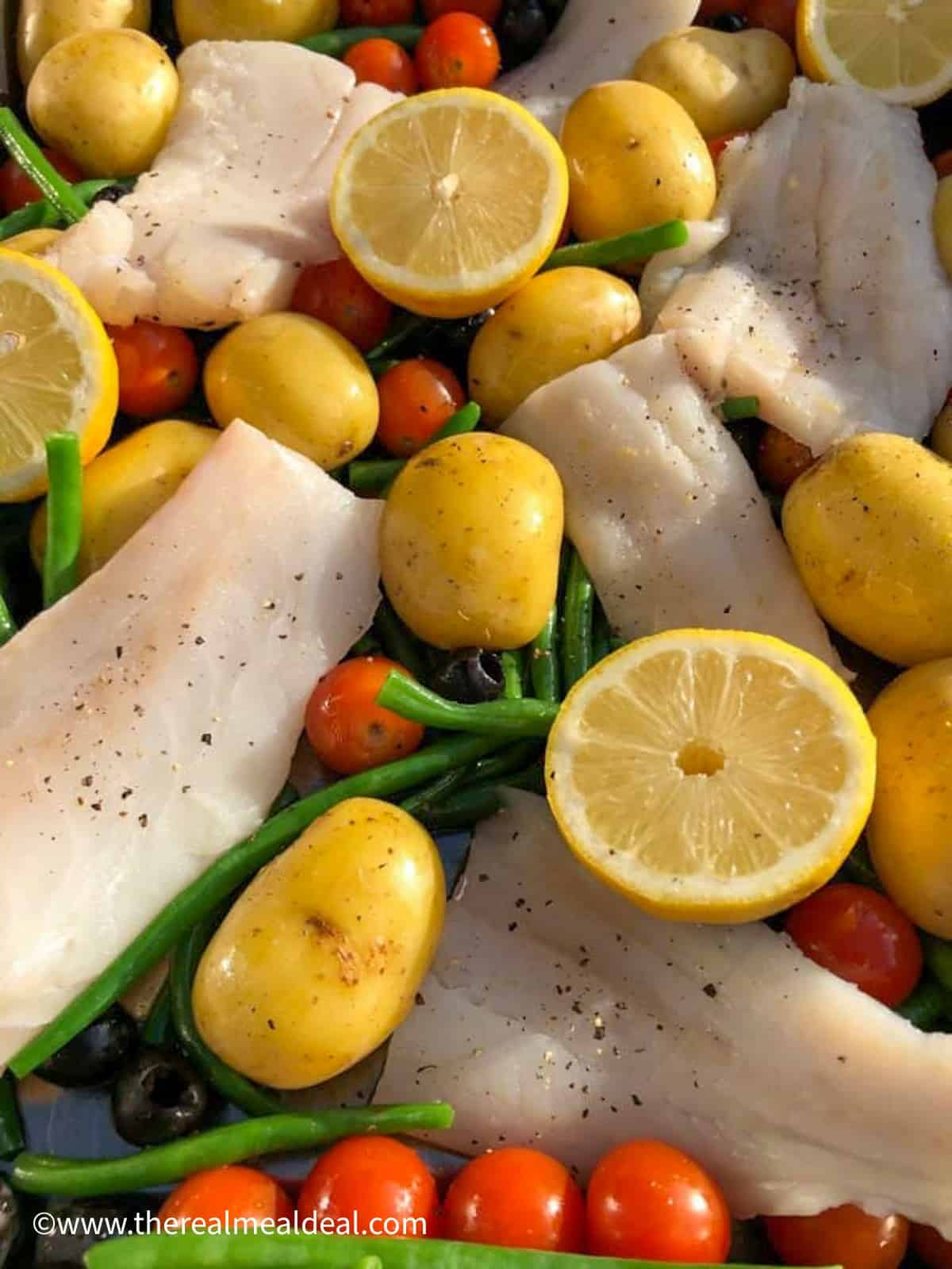 cod green beans cherry tomatoes black olives and new potatoes in tray ready for roasting seasoned with black pepper