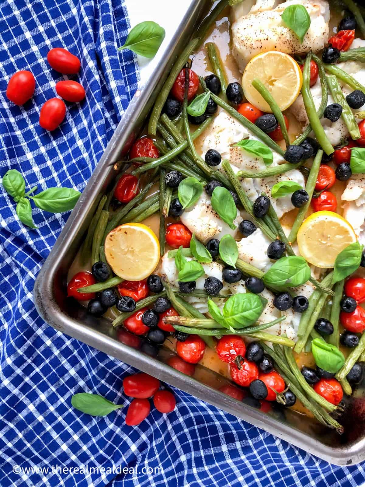 baked cod black olives cherry tomatoes and green beans in metal baking tray topped with fresh basil leaves