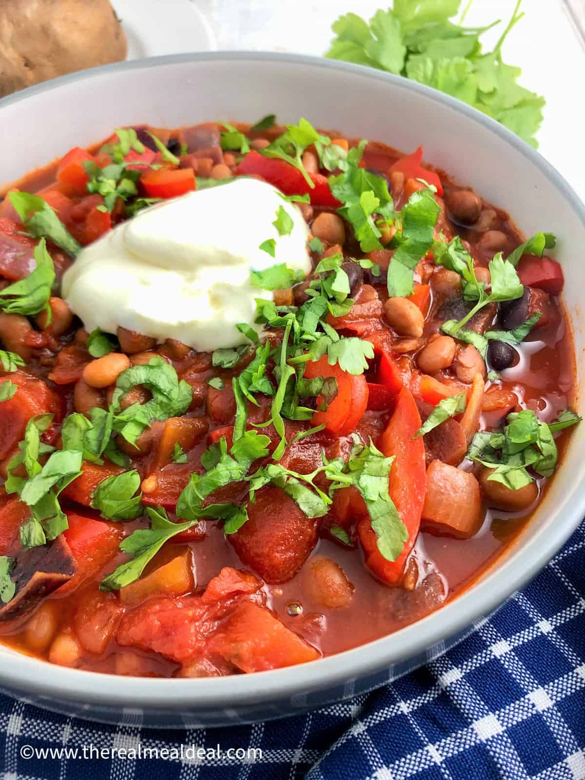 bean goulash topped with fresh parsley and soured cream in a bowl