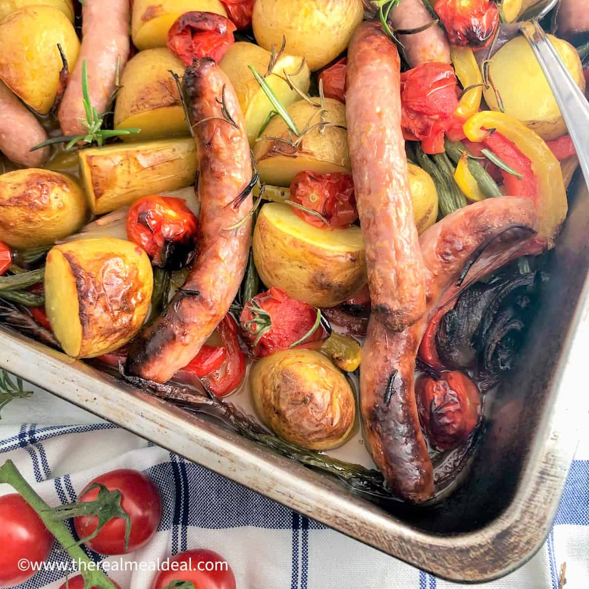roasted new potatoes green beans, tomatoes and peppers in tray with sausages and rosemary