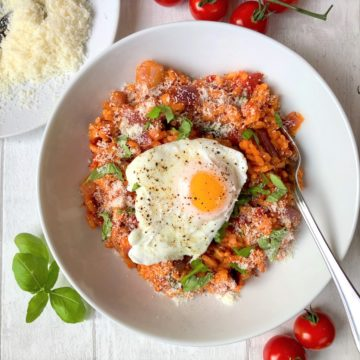 tomato and basil risotto topped with paoched egg sprinkled with black pepper and parmesan cheese