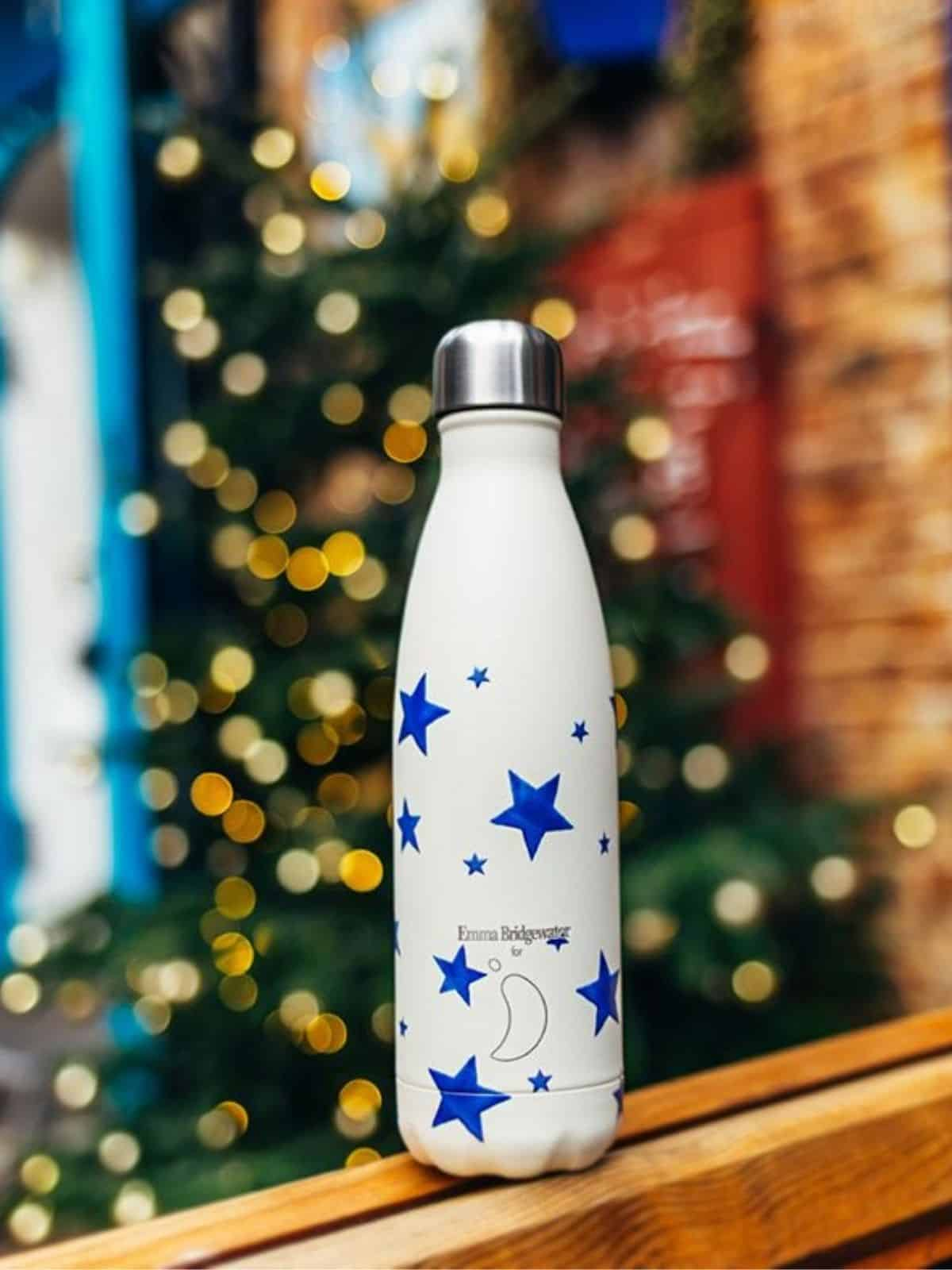 white reusable water bottle recorated with blue stars on a wooden ledge with christmas tree in background