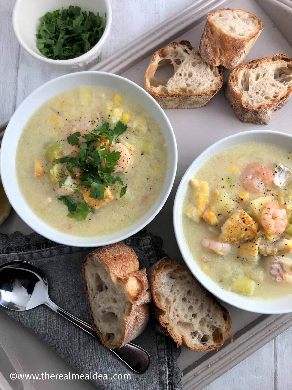 two bowls of smoked haddock and prawn chowder on a tray with sliced baguette