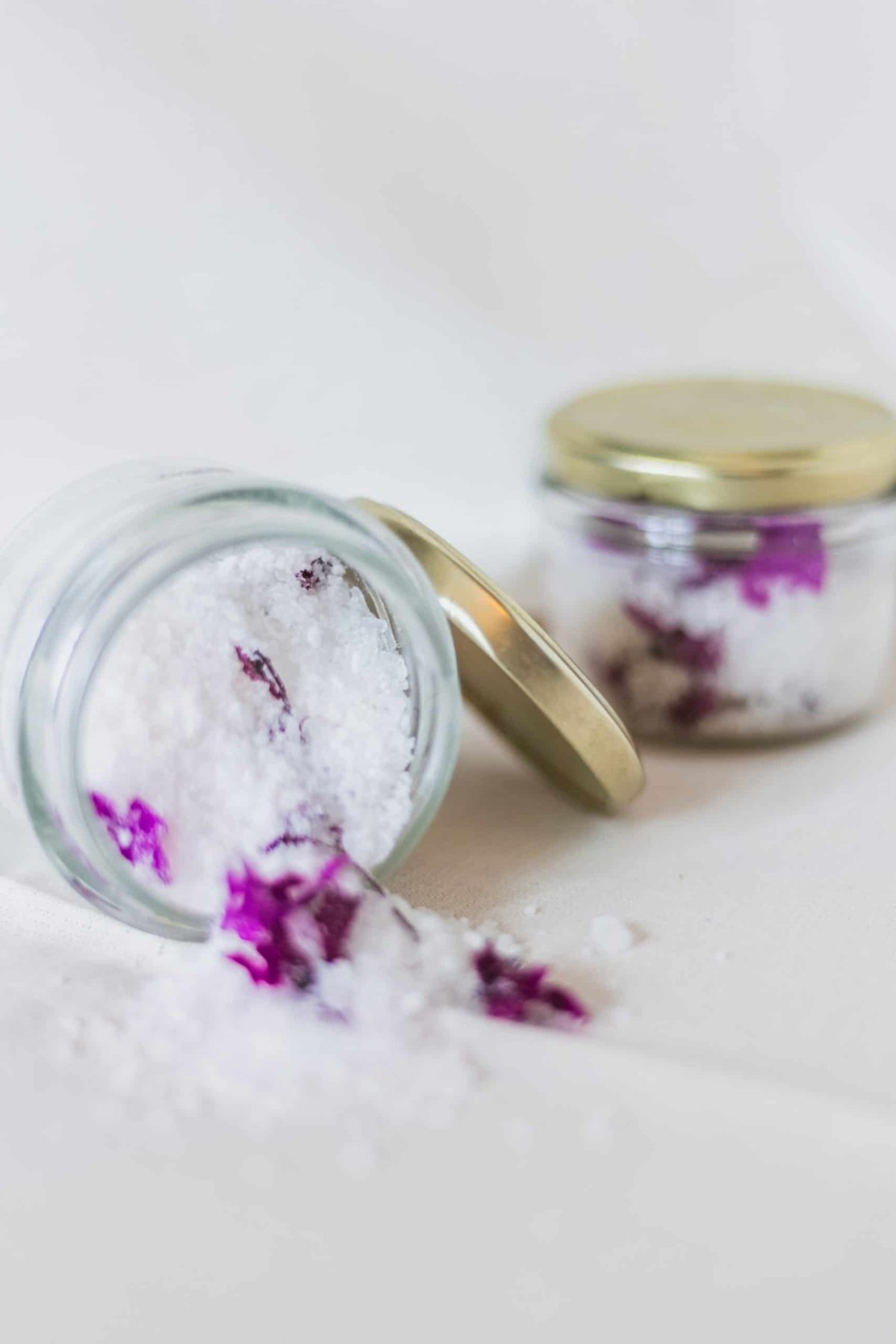 overtunred jar of bath salts containing salts and purple petals