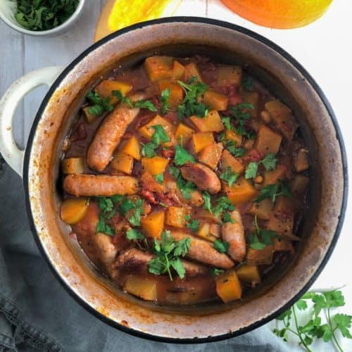sausage and pumpkin casserole in dish topped with fresh parsley