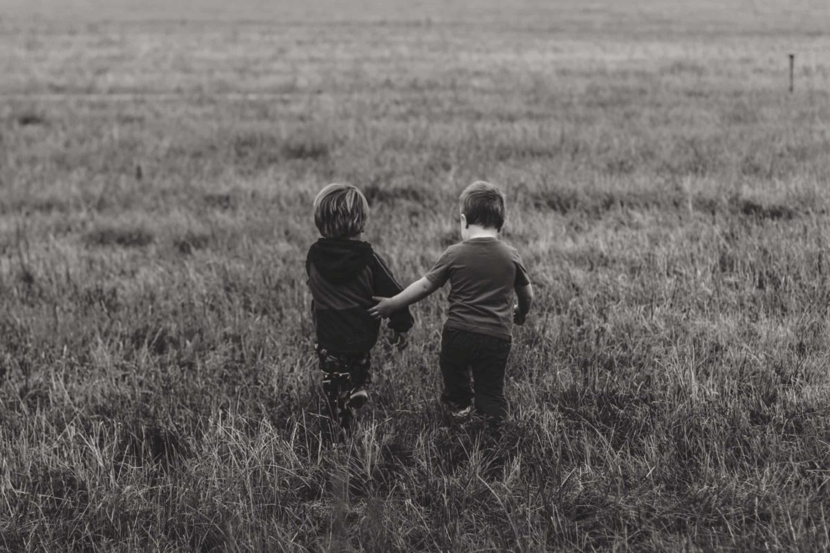 two children walking in a field together